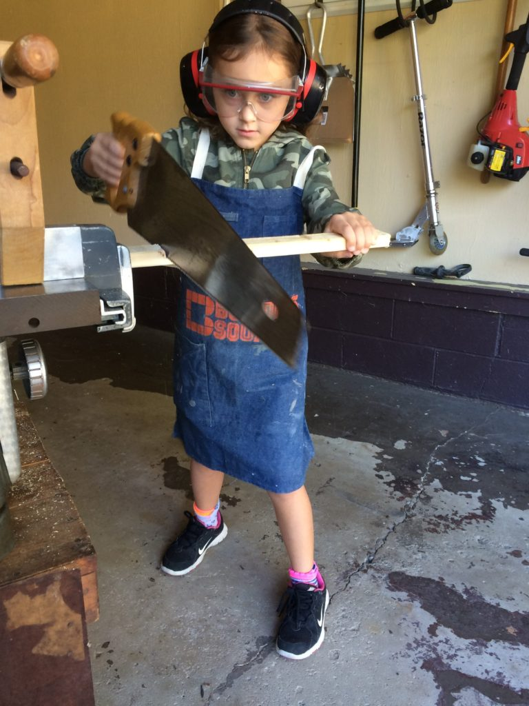Child cutting a board with a hand saw