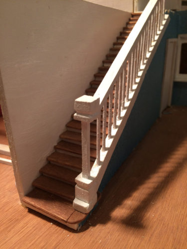 stairs installed in dollhouse with bannister, handrail, and spindles.